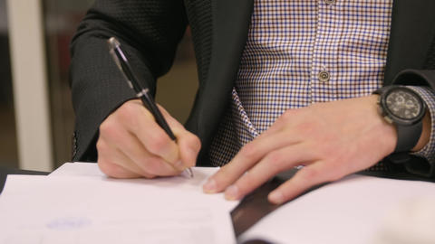 Businessman doing paperwork in the office. Young male filling checklist sitting Footage