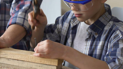 Boy hammering nail, father supports him, repair workshop, family business Live Action