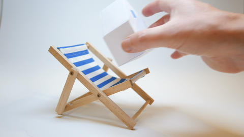 an insurer's hand puts a paper house on a deckchair to symbolize nothing fears Footage