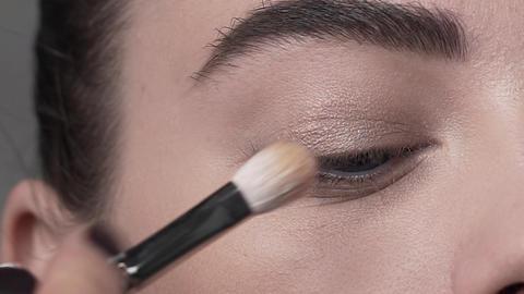 Macro shot of applying makeup to the woman's eyelid, evening makeup, smokey eyes Live Action