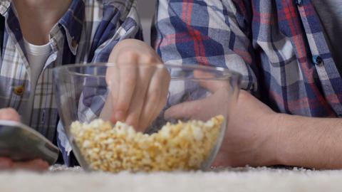 Male hands taking popcorn from glass bowl during watching tv, unhealthy food Live Action
