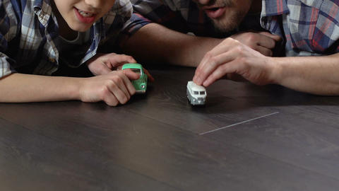 Boy and father competing in toy cars racing on the floor at home, playing game Live Action