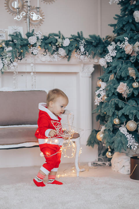 Little boy the kid in the red sweater on the Christmas tree フォト
