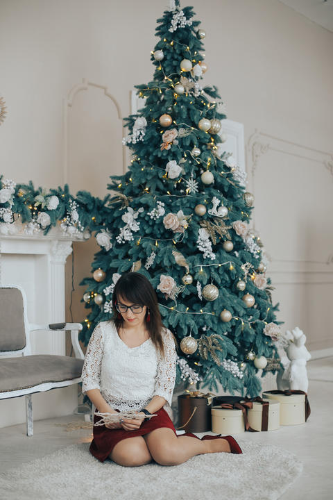 Girl in white sweater and glasses on Christmas decoration with Christmas tree Fotografía