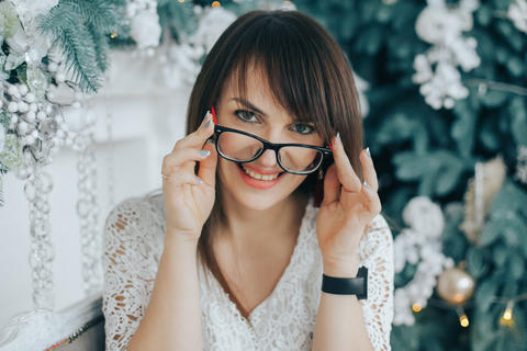 Portrait of smiling woman in glasses with Christmas decor フォト