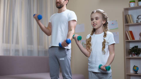 Father and daughter training with dumbbells at home, fitness family leisure Footage