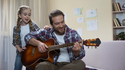 Talented girl singing while father playing guitar, home concert, musical hobby Footage