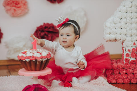 Curious baby girl poking finger in his first birthday cake Photo
