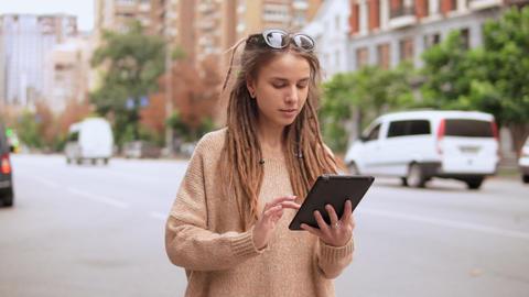 millennial girl using gadget outdoors Live Action