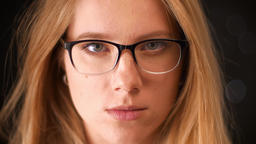 Portrait of nice blonde spectacled caucasian woman looking in camera closely Footage