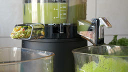 Green juice. Slow juicer is making kale, mint and apple juice Footage