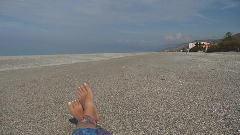 Bare feet of woman lying on pebble beach. Rest near the sea on sunny day. First Footage