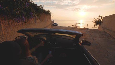 Woman parks cabriolet car near a beach for looking on beautiful sunset over sea Footage