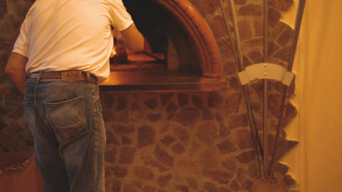 Italian chef puts a pizza into traditional wood-fired stone oven using peel Live Action