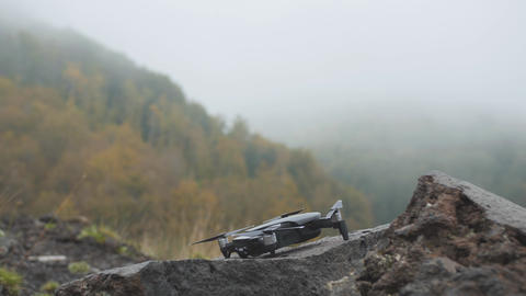 Drone takes off from rough stone in misty mountains. Fog in autumn forest GIF