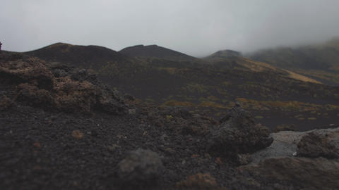 Black stones on lifless volcano slopes. Low gray clouds covere mountain top GIF