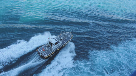 Pilot boat float fast from ferry towards the seaside city. Deep blue sea Footage