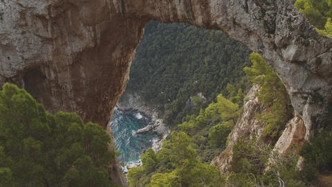 Birds fly over sea shore. View through natural arch on the top of the mountain Live Action