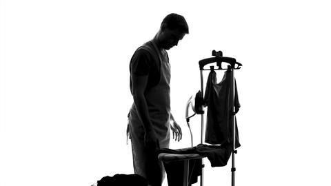 Single man ironing t-shirt for first time, household duties, bachelor lifestyle Footage