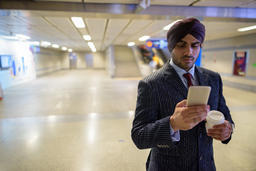 Indian Sikh businessman at subway train station using phone and holding coffee Fotografía