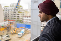 Indian businessman looking at construction development site with skyscrapers フォト