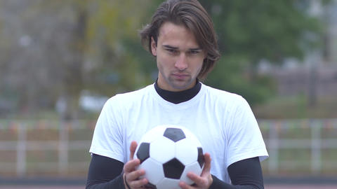 Portrait of a young guy in a sports t-shirt holding a soccer ball in his hands Footage