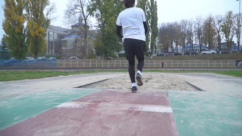 Handsome young man in sportswear accelerates and jumps in the sand Sand scatters Footage