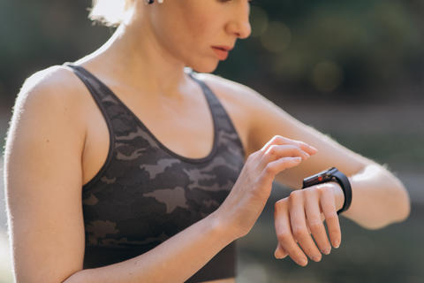 Woman using her smartwatch touchscreen wearable technology device in morning フォト