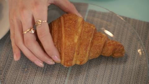 Female hand taking croissant from glass plate at table in cafe close up フォト