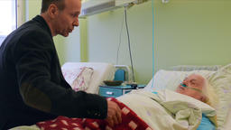 Man is talking to an old, ill lady in hospital Footage