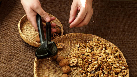 Woman hand is cracking a walnut with metal nutcracker Archivo