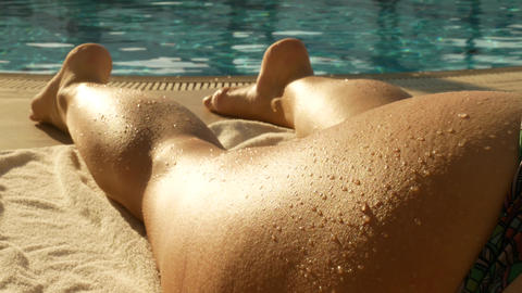 Woman's legs sunbathing on the beach lounger GIF