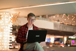 Young Handsome Hipster Man Using Laptop In The City At Night フォト