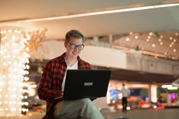 Young Happy Hipster Man Using Laptop In The City At Night Photo