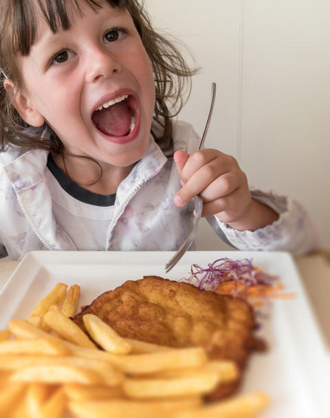 Little Italian girl eating breaded meat and french fries フォト