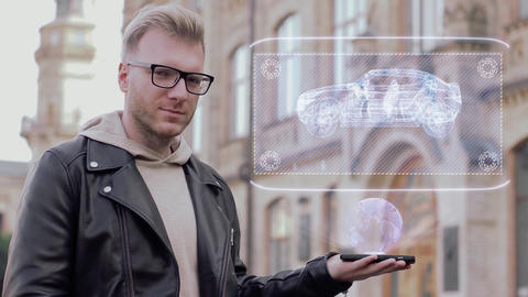 Smart young man with glasses shows a conceptual hologram modern Suv Live Action