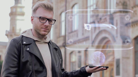 Smart young man with glasses shows a conceptual hologram eyeglasses Live Action