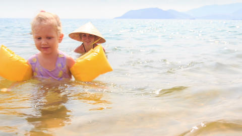 Little Girl in Safety Armbands Swims out of Azure Sea Live Action