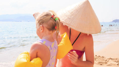 Mother Takes off Armbands from Little Girl on Sand Beach Live Action