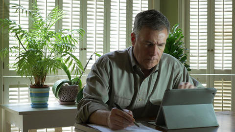 Mature Man At Home With Tablet Pc Working On Financials stock footage