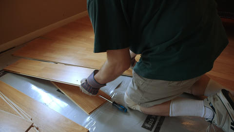 Over shoulder of workman removing laminate flooring Footage