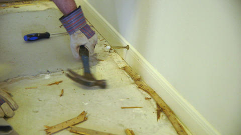 DIY demolition project of carpet tack strips by homeowner Footage
