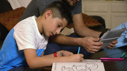 Young boy drawing while his dad watches Footage
