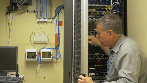 Network administrator checking patch cables in a server rack Footage