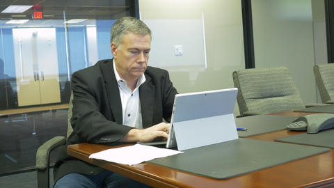 businessman in a corporate conference room using a tablet pc Footage