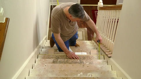 carpenter fitting in stair riser and measuring for the step Footage