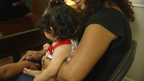 Pretty Hispanic mother holds her adorable baby girl during consultation Footage