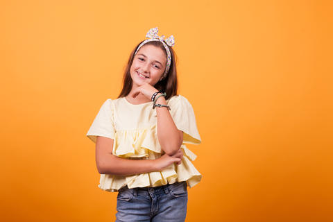 Little girl smiling on yellow background in studio Photo