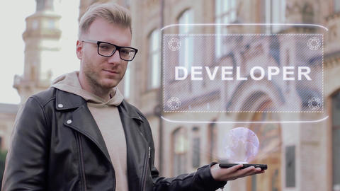 Smart young man with glasses shows a conceptual hologram Developer Live Action