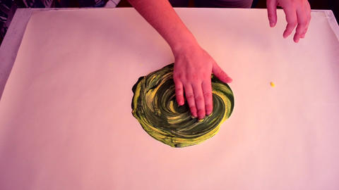 Mixing paint yellow with green and hands smearing on white surface Archivo